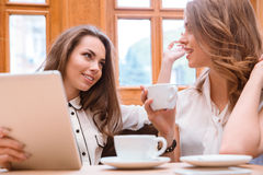 Amies buvant du café et parlant en café Photo libre de droits