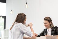 Amies caucasiennes s'asseyant au café et tenant des mains tout en buvant du café Photographie stock