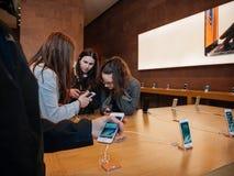 Amies d'adolescent examinant le dernier iphone à Apple Store Image stock