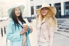 Amies dans des chapeaux avec du café Photo stock
