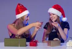 Amies dans des chapeaux de Noël avec des cocktails Photos libres de droits
