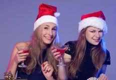 Amies dans des chapeaux de Noël avec des cocktails Image stock