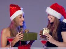 Amies dans des chapeaux de Noël avec des cocktails Photographie stock