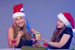 Amies dans des chapeaux de Noël avec des cocktails Photos stock