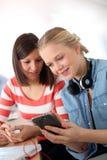Amies dans la classe utilisant des smartphones Image stock