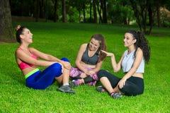 Amies dans les vêtements de sport ayant l'amusement sur l'herbe Photographie stock