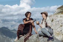 Amies dans les vêtements folkloriques riant et ayant le thé sur le m Photographie stock libre de droits
