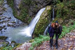 Amies dans les vacances posant par la cascade Photo libre de droits
