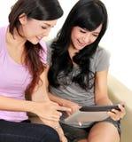 Amies de femmes à la maison utilisant l'ordinateur de comprimé Photographie stock