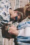 Amies de femmes avec des lunettes de soleil se regardant se trouvant Photos stock