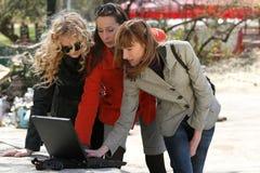 Amies de femmes avec l'ordinateur portatif extérieur Photo libre de droits