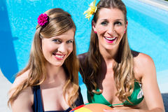 Amies de femmes avec la boule de l'eau se reposant à la piscine Photographie stock libre de droits