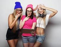 Amies de hippie avec le comprimé numérique Photo stock