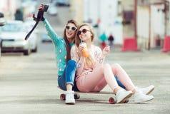 Amies de hippie prenant un selfie dans la ville urbaine Photos stock
