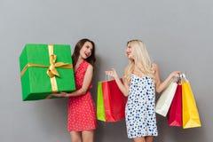 Amies de jeunes dames étonnantes avec les paniers et le cadeau Photographie stock libre de droits