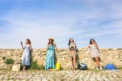 Amies de jeunes femmes à l'aide du smartphone dehors Image stock