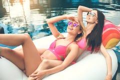 Amies de jeunes femmes dans l'amusement de piscine Image libre de droits