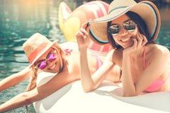 Amies de jeunes femmes dans l'amusement de piscine Photos stock