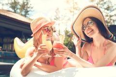 Amies de jeunes femmes dans l'amusement de piscine Image stock