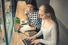 Amies de jeunes femmes dans un temps gratuit de café Photos stock