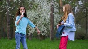 Amies de l'adolescence mignonnes jouant sa guitare dehors les petites filles chantent des chansons pour peigner des cheveux et la banque de vidéos