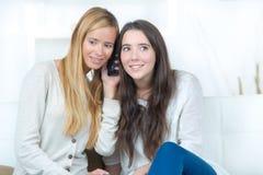 Amies de l'adolescence partageant la conversation téléphonique Images libres de droits