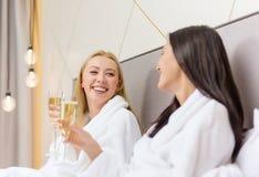 Amies de sourire avec des verres de champagne dans le lit Photographie stock