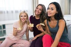 Amies de sourire avec la pizza regardant l'appareil-photo Photographie stock libre de droits