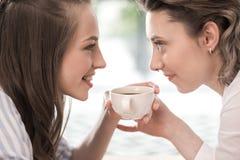 Amies de sourire buvant le café et regarder l'un l'autre Photos stock