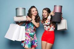 Amies de sourire dans des vêtements colorés avec beaucoup de sacs après l'achat Images stock