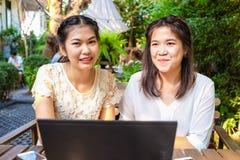 Amies de sourire de femmes avec la boisson chaude utilisant l'ordinateur portable en café Photographie stock