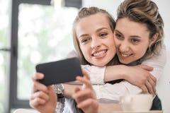 Amies de sourire embrassant et prenant le selfie sur le smartphone au café Images stock