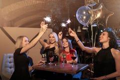 Amies de sourire heureuses dans des robes célébrant la nouvelle année dans la barre tenant les cierges magiques rougeoyants Photos libres de droits