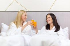 Amies de sourire prenant le petit déjeuner dans le lit Photo libre de droits
