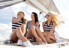 Amies de sourire s'asseyant sur la plate-forme de yacht Photographie stock