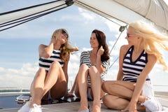 Amies de sourire s'asseyant sur la plate-forme de yacht Photo stock