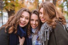 Amies de sourire se tenant en parc d'automne Photos stock
