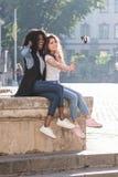 Amies drôles ayant l'amusement en prenant des photos utilisant le bâton de selfie tout en se reposant sur la fontaine dans le cen Image stock