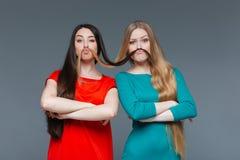 Amies drôles faisant la moustache avec leurs cheveux Images libres de droits