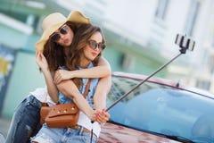 Amies du selfie deux d'été les belles s'approchent de la voiture Photos stock