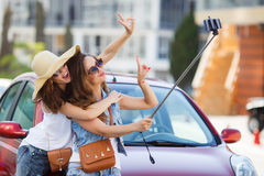 Amies du selfie deux d'été les belles s'approchent de la voiture Image stock