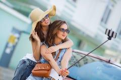 Amies du selfie deux d'été les belles s'approchent de la voiture Photo stock