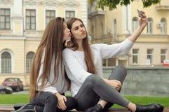 Amies dupant autour et grimace comme ils font la photo de selfie Images libres de droits