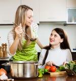 Amies faisant cuire quelque chose avec des légumes Photos libres de droits