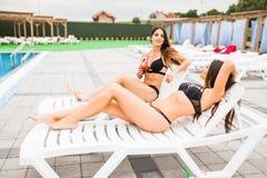 Amies faisant tinter des verres avec des cocktails au salon au poolside en été Images libres de droits