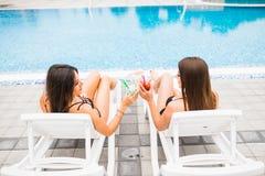 Amies faisant tinter des verres avec des cocktails au salon au poolside en été Photos stock