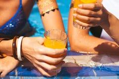 Amies faisant tinter des verres avec des cocktails à la barre de poolside Photo stock