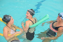 Amies gaies ayant l'amusement dans la piscine Image stock