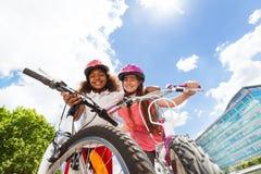 Amies heureuses étreignant et tenant des bicyclettes Photos libres de droits