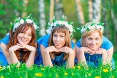 Amies heureuses 30 ans en parc sur l'herbe verte Photographie stock